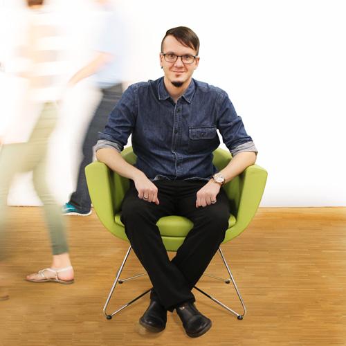 Mitarbeiter Dennis sitzt auf dem grünen Stuhl